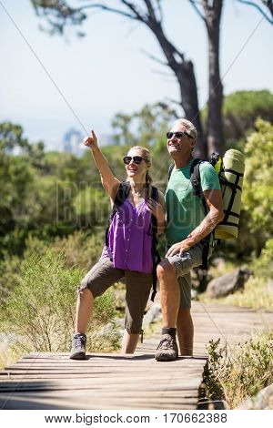 Couple pointing and smiling during a hike on the wood