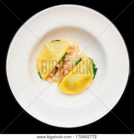 Ravioli-like dish with crayfish, apples and herbs isolated on black background