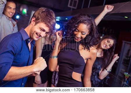Happy friends dancing together in a nightclub