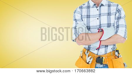 Mid section of handy man standing with arms crossed against yellow background
