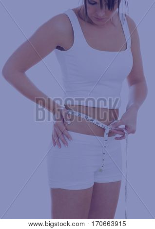 Woman in sportswear measuring waist with a measurement tape against white background