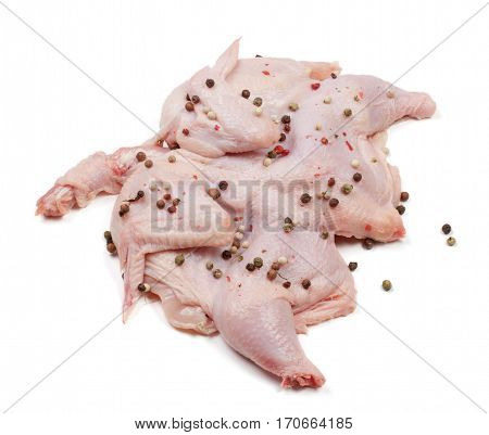 raw chicken carcass with peppercorns isolated on white background.