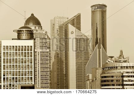 SHANGHAI CHINA - MARCH 25: Pudong district skyscrapers view from The Bund waterfront area on March 25 2016 in Shanghai China. Pudong is a district of Shanghai located east of the Huangpu River. Sepia toned photo