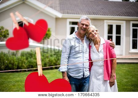 Portrait of smiling senior couple embracing each other against hearts hanging on line