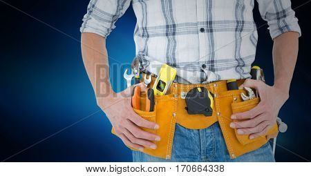 Mid section of handyman with tool belt around his waist against blue background