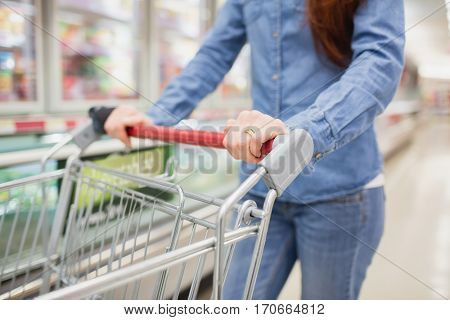 Cropped image of woman pushing trolley in aisle at supermarket