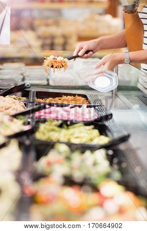 Close up view of hands picking prepared meals in grocery store