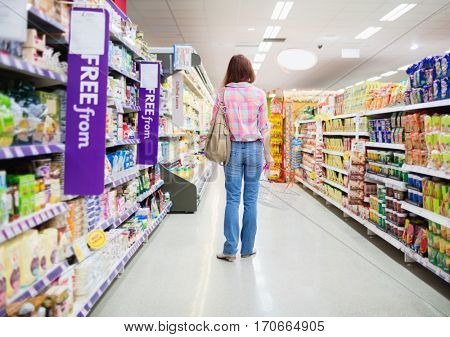 Rear view of woman standing in aisle at supermarket