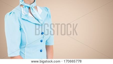 Mid section of air hostess standing against beige background