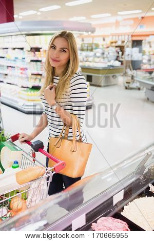 Blonde woman posing with trolley in grocery store