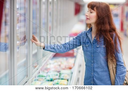 Concentrated woman buying frozen food in supermarket