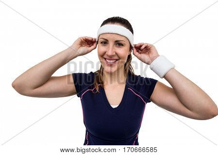 Female athlete wearing headband and wristband on white background