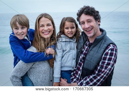 Portrait of parents smiling while carrying children at sea shore