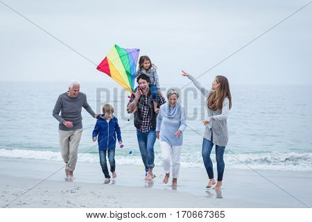 Full length of multi-generation family running at sea shore against sky