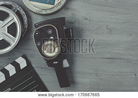 Old movie camera with film reels and a clapper board lying on the painted table