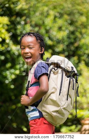 Smiling boy carrying backpack in the park
