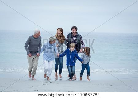 Full length of happy multi-generation family enjoying at sea shore against sky
