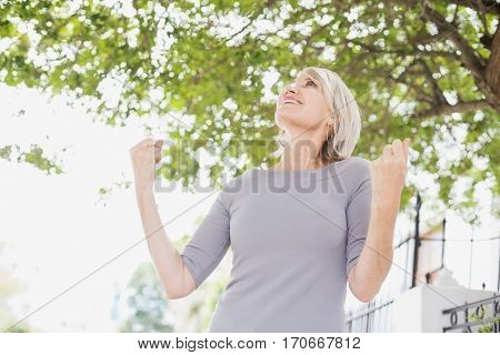 Happy woman with raised fists looking up