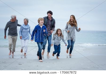 Full length of happy multi-generation family running at sea shore against sky