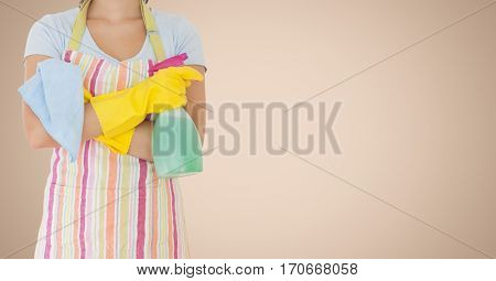 Mid section of female cleaner standing with napkin and spray bottle against beige background