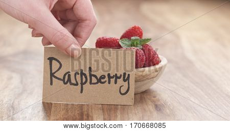 young female hand putting paper card near bowl of blueberries on table, 4k photo