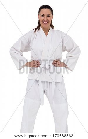 Female karate fighter standing with hand on hip on white background