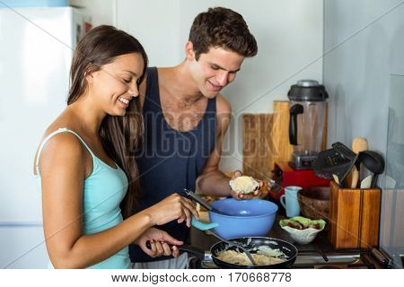 Happy young couple cooking food together in kitchen at home