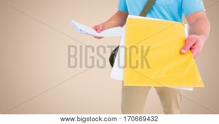 Mid section of delivery man with documents against beige background