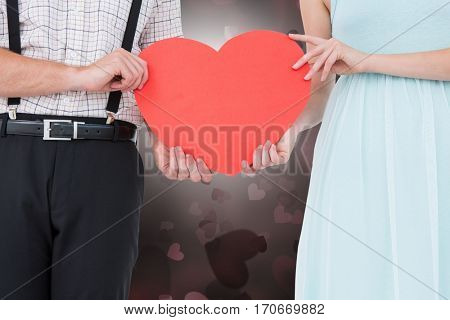 Mid-section of couple holding a red heart against digitally generated background