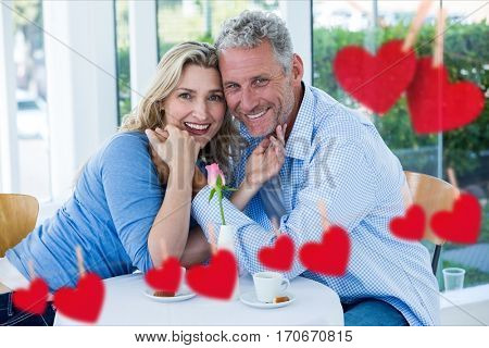 Composite image of romantic couple enjoying together in a restaurant with red hearts hanging on line