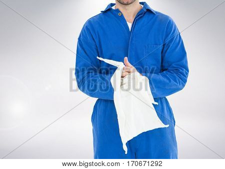 Mid section of mechanic holding napkin against grey background