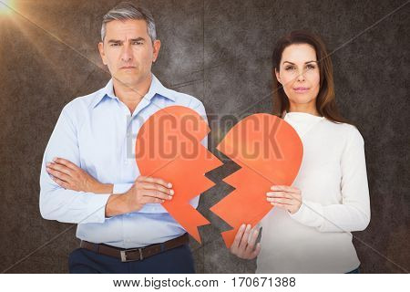 Portrait of couple holding broken heart shape paper against grey background