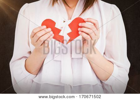 Woman holding broken heart paper against grey background