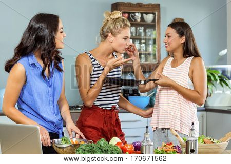 Female friends tasting food in kitchen at home