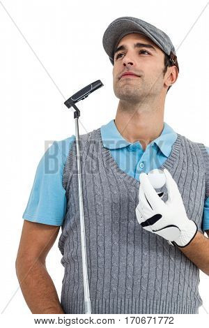 Golf player standing with golf ball and golf club on white background