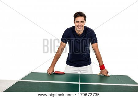 Confident male athlete leaning on hard table on white background