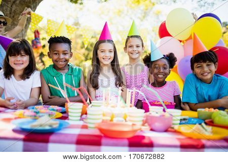 Group of children smiling and posing during a birthday party on a park