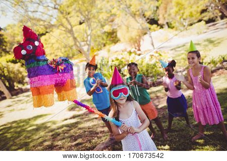 Little girl is going to broke the pinata for their birthday in a park