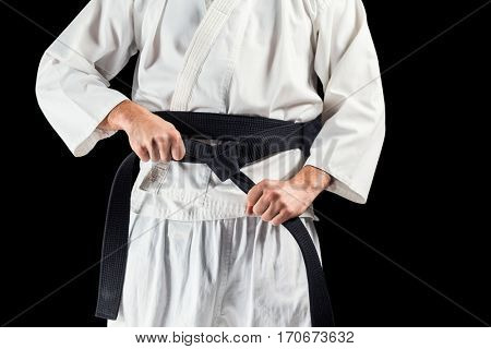 Mid section of fighter tightening karate belt on black background