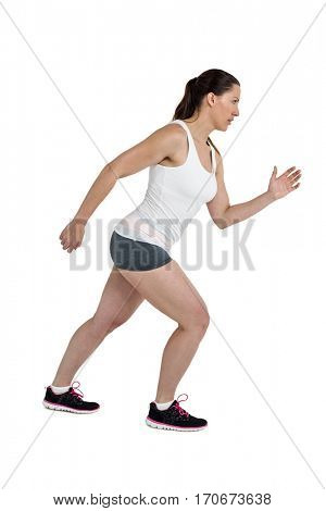 Side view of energetic female athlete running on white background