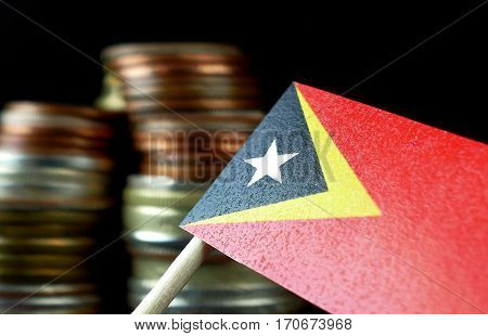 East Timor Flag Waving With Stack Of Money Coins Macro