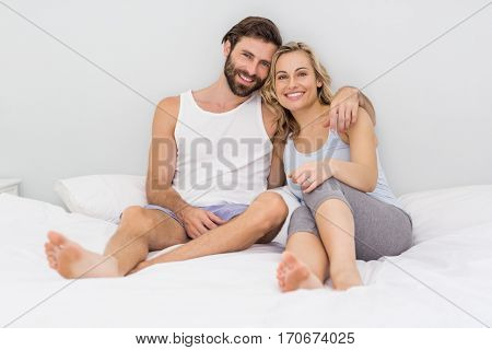 Portrait of romantic couple sitting on bed in bedroom