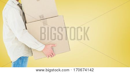 Mid section of delivery man carrying boxes against yellow background
