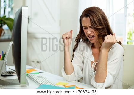 Irritated businesswoman in front of computer at desk in office