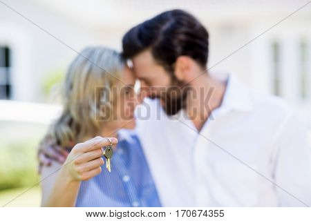 Happy couple embracing each other holding house key