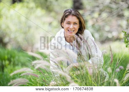 Portrait of happy woman crouching on grassy field