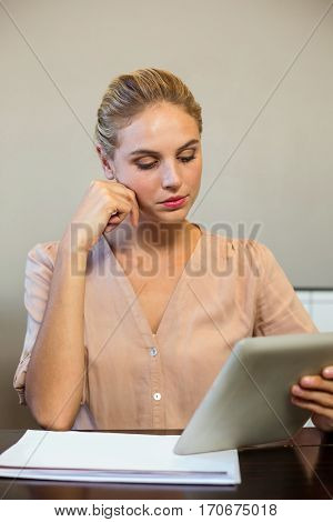 Focused businesswoman holding digital tablet in office