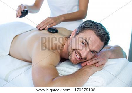 Portrait of man receiving a hot stone massage from masseur