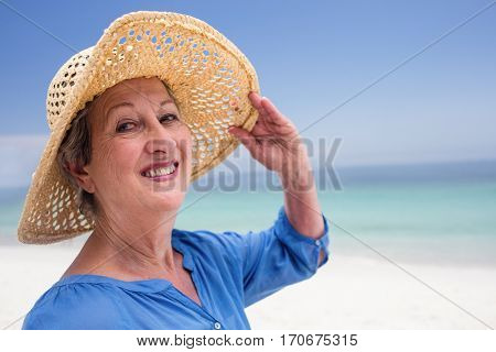 Close-up of happy senior woman in beach hat and smiling on the beach