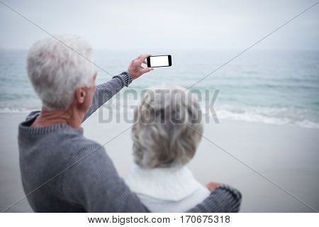 Senior couple taking a selfie on mobile phone at beach